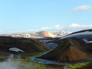 This is a neat shot because it shows so many elements of the landscape: mountains; clear, glacial streams; steam rising from a geyser (bottom left); endless skies; and patches of snow covered with volcanic ash on rolling hills.