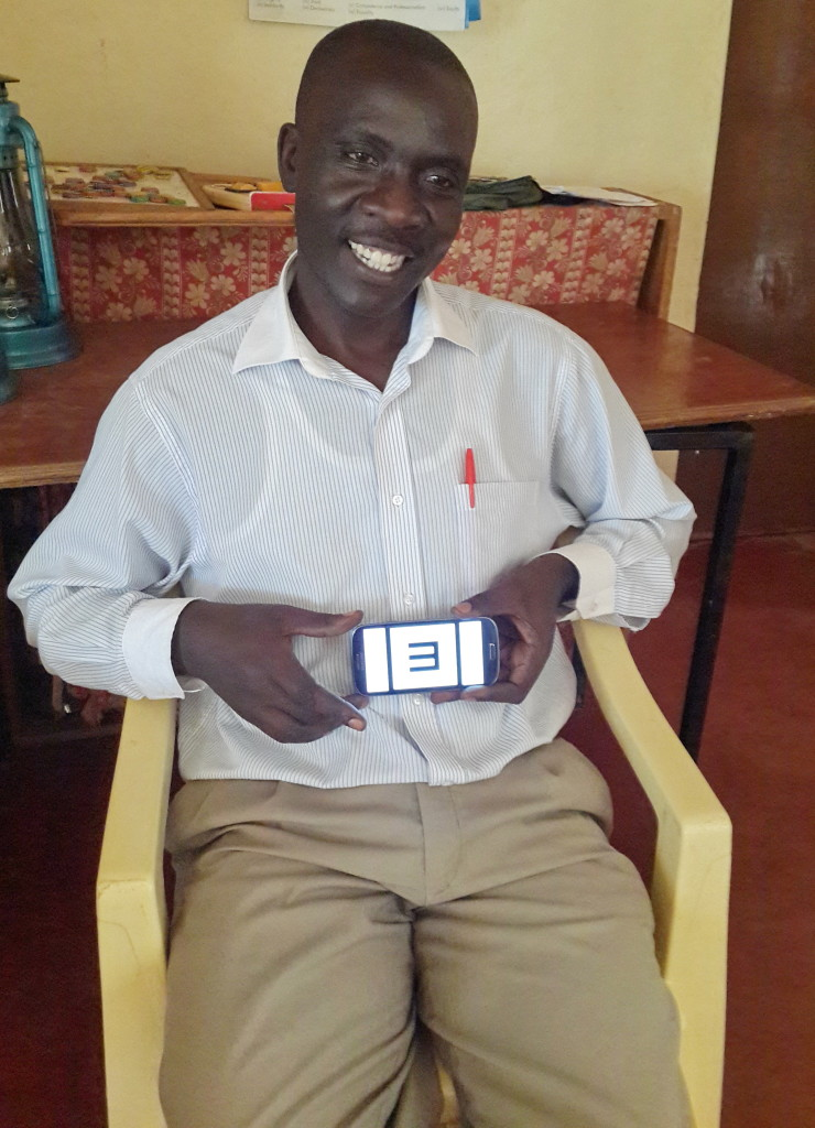 Proud teacher Wilberforce Nyukuri demonstrates the PEEK app screen.